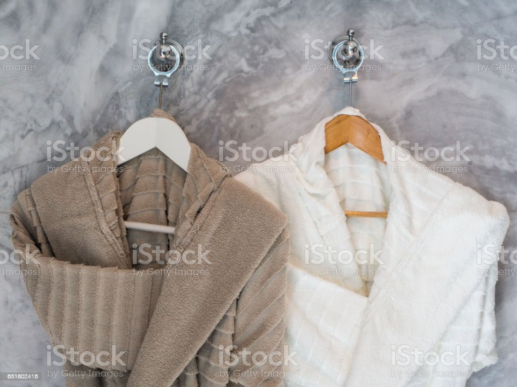 White and brown Clean bathrobes hanging on hanger - foto stock