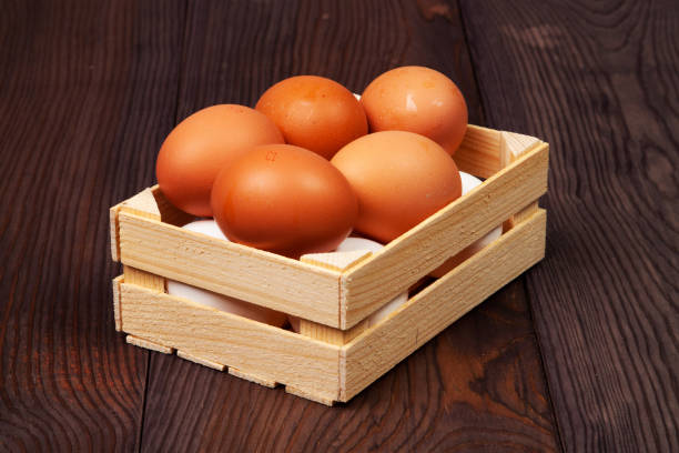 Cтоковое фото White and brown eggs in wooden crate on wooden background.