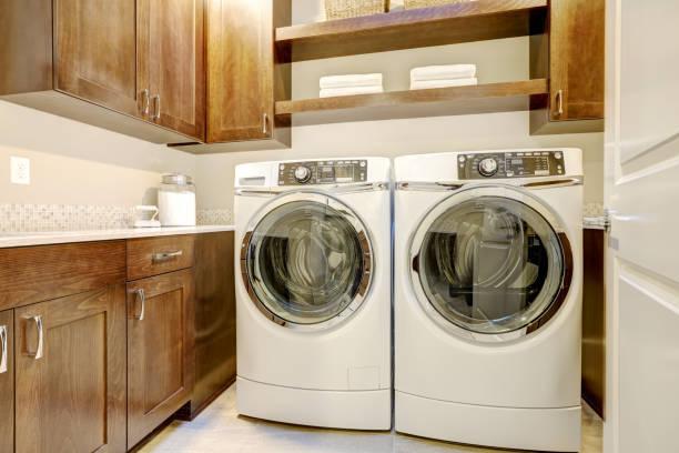 近代的な設備を持つ白と茶色のランドリー ルーム - 衣類乾燥機 ストックフォトと画像