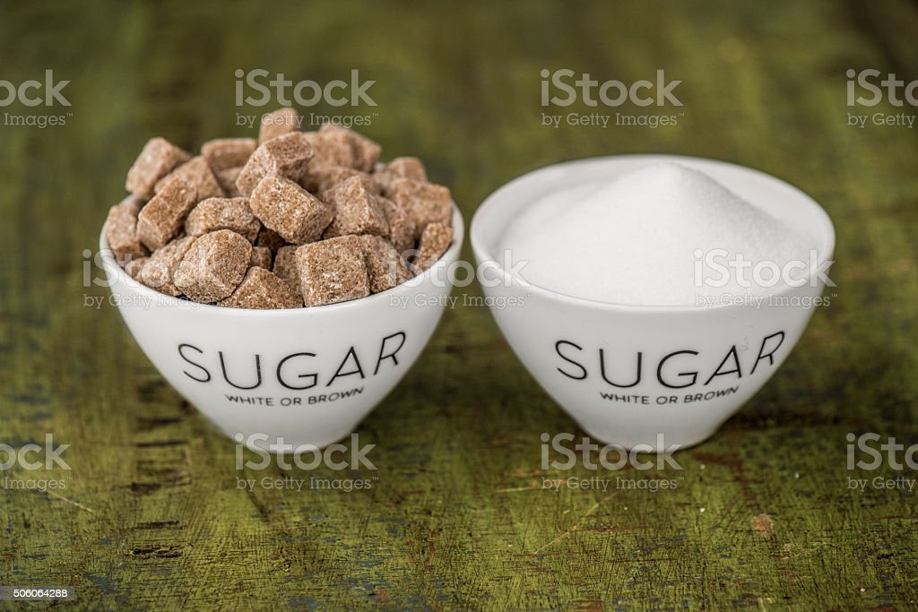 White and brown sugar on green stock photo