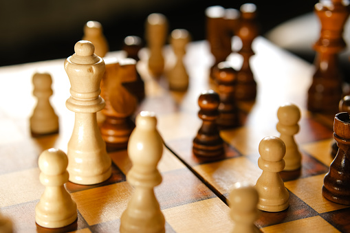 White and brown wooden chess pieces close up. Home board game.