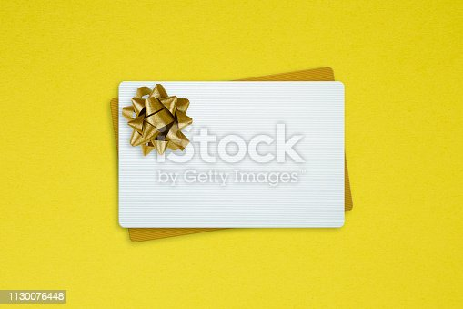 White And Golden Gift Cards With Gold Bow Ribbon on yellow background