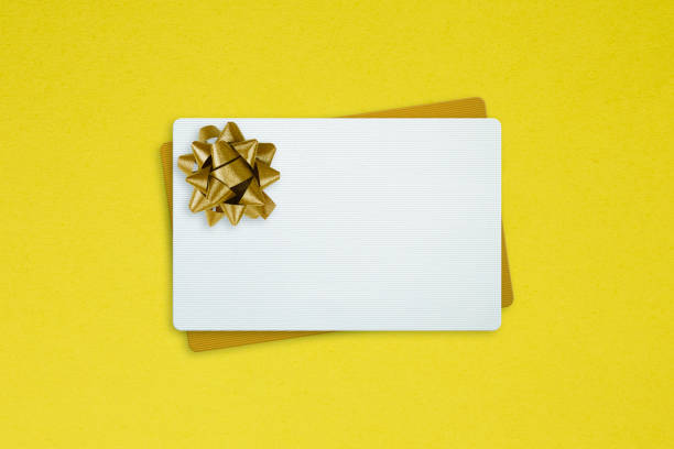 White And Golden Gift Cards With Gold Bow Ribbon White And Golden Gift Cards With Gold Bow Ribbon on yellow background gift card stock pictures, royalty-free photos & images