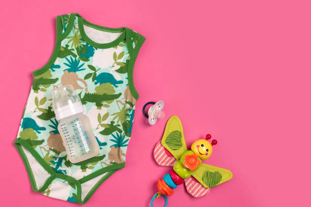 white and green bodysuit and bottle on pink background. things for babies. top view - sport set competition round stock photos and pictures