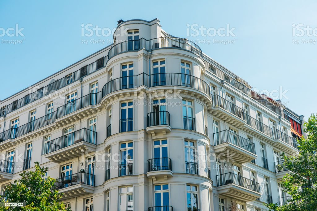 white and luxury corner house for real estate themes with curved balconies and clean colors stock photo