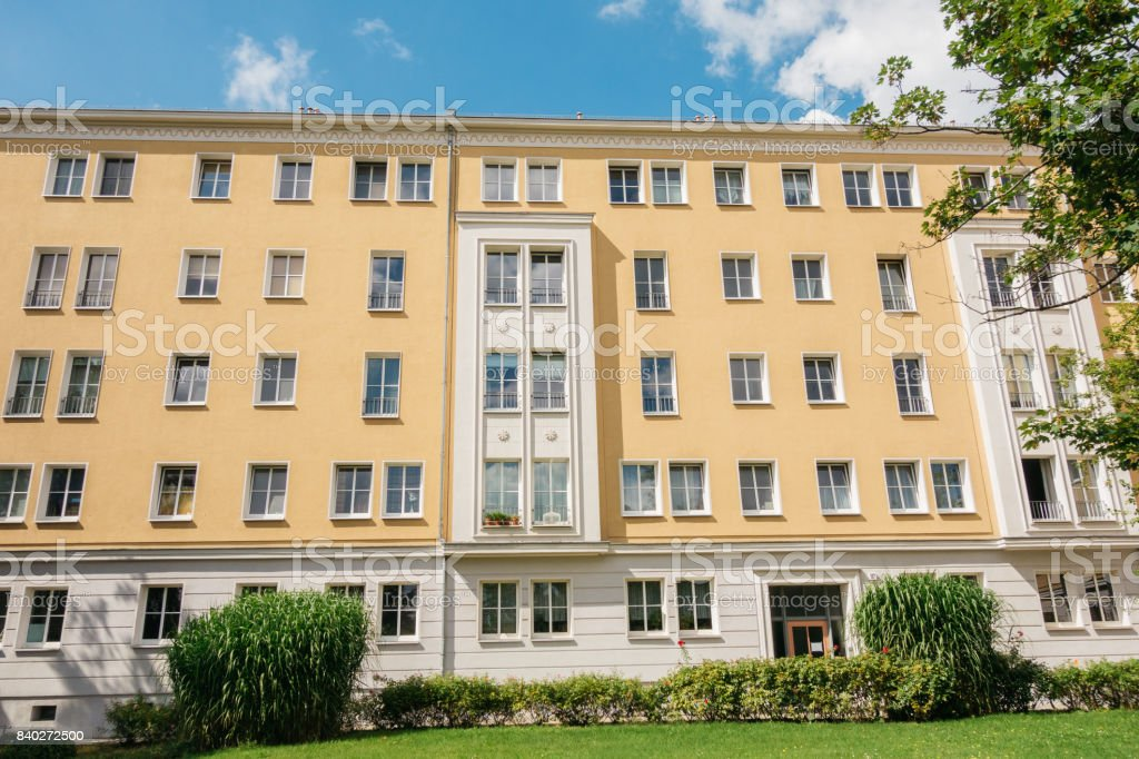 white and orange apartment house exterior green grass in the foreground stock photo