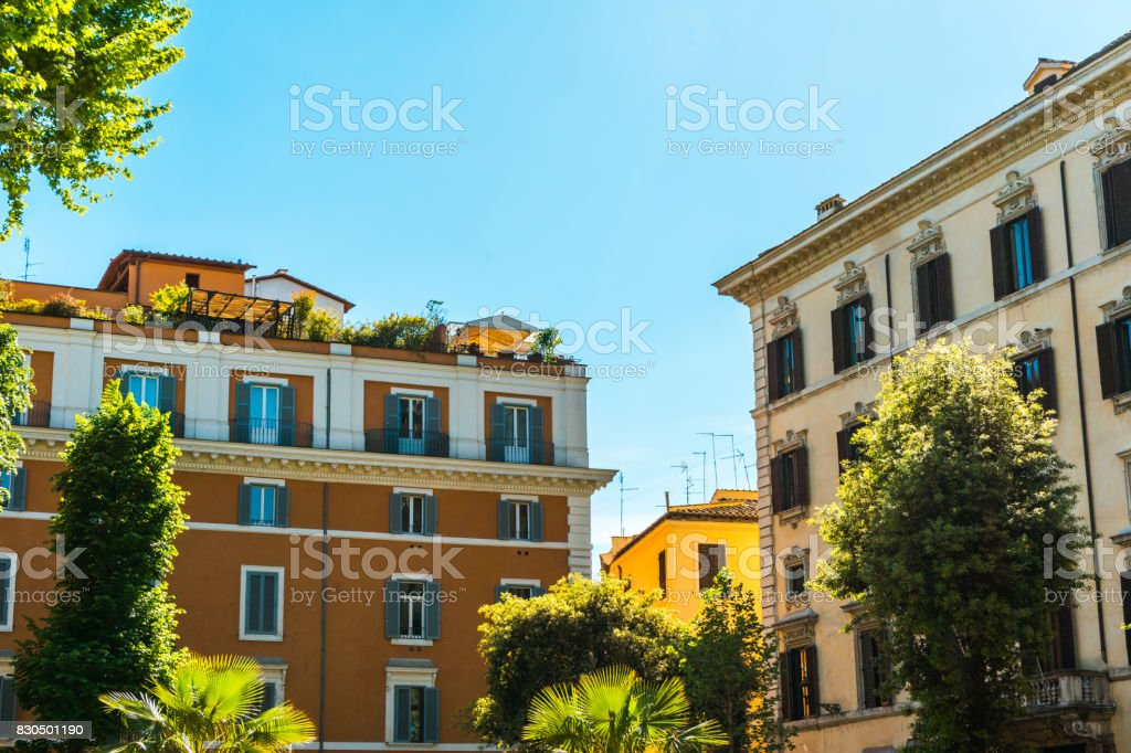 white and orange buildings with beautiful plants in the front stock photo