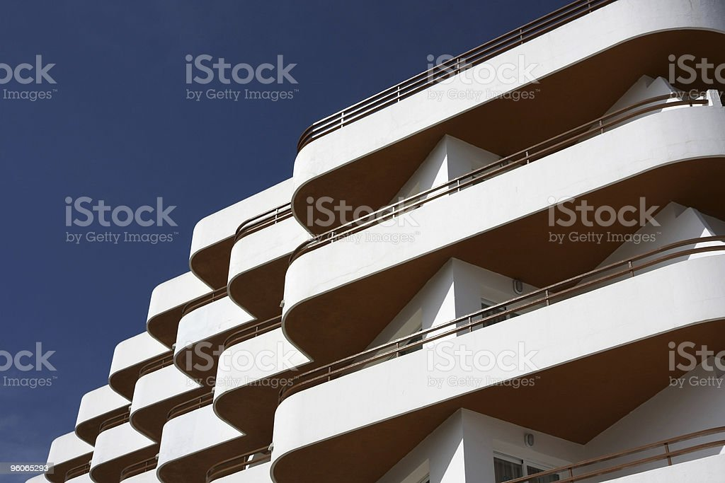 white and orange hotel facade with balconies stock photo