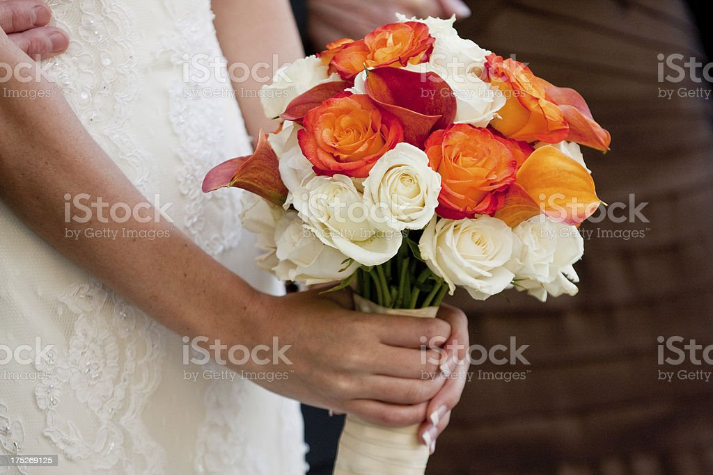 White and Orange Rose Wedding Bouquet in Bride's Hands royalty-free stock photo