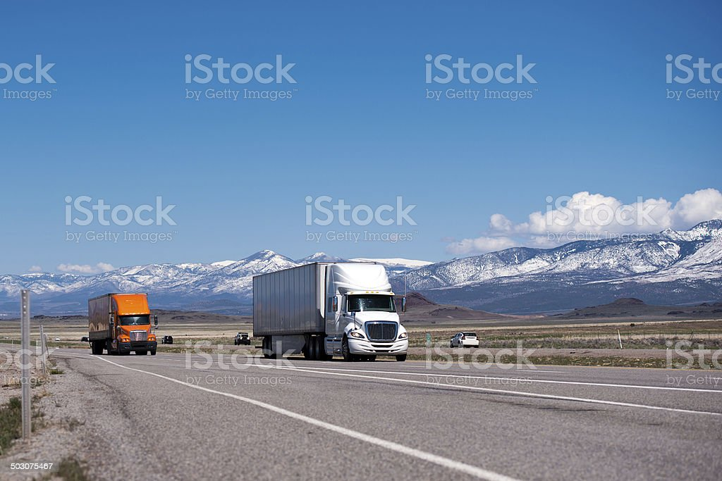 White and orange semi trucks and trailers on high way stock photo