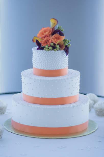 weiß und orange dreistufige hochzeitstorte - orange hochzeitstorten stock-fotos und bilder