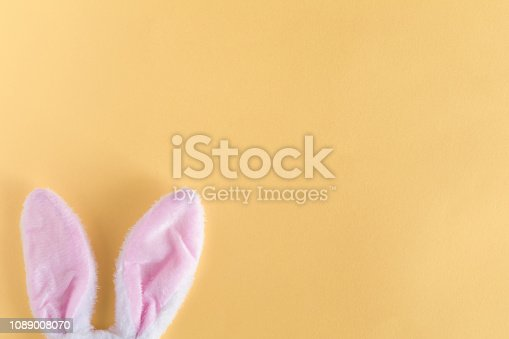 White and pink Bunny or rabbit ears on yellow pastel background. Easter minimal concept. Flat lay and view from above