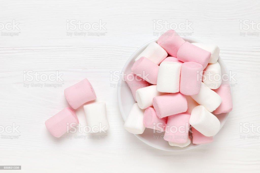 Weiß-rosa Marshmallow auf eine Untertasse auf einer weißen Fläche aus Holz – Foto