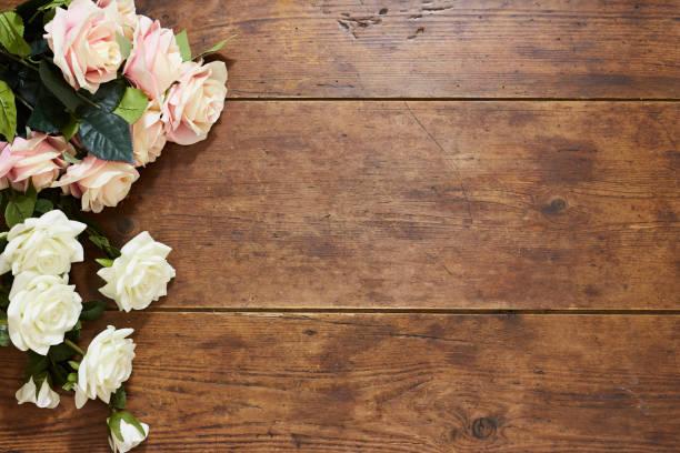 weißen und rosa rosen auf rustikalen holz hintergrund - holzblumen stock-fotos und bilder