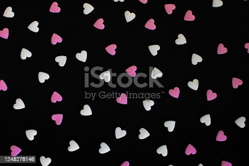 157527860 istock photo White and pink sugar hearts on dark background 1248278146