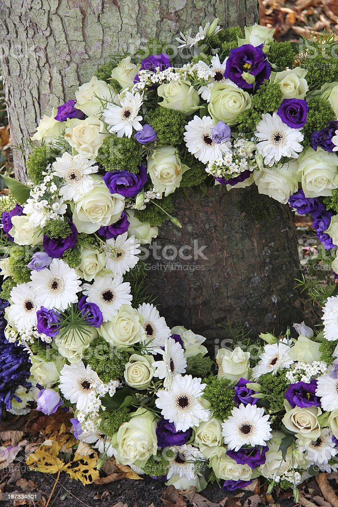 A white and purple sympathy wreath stock photo