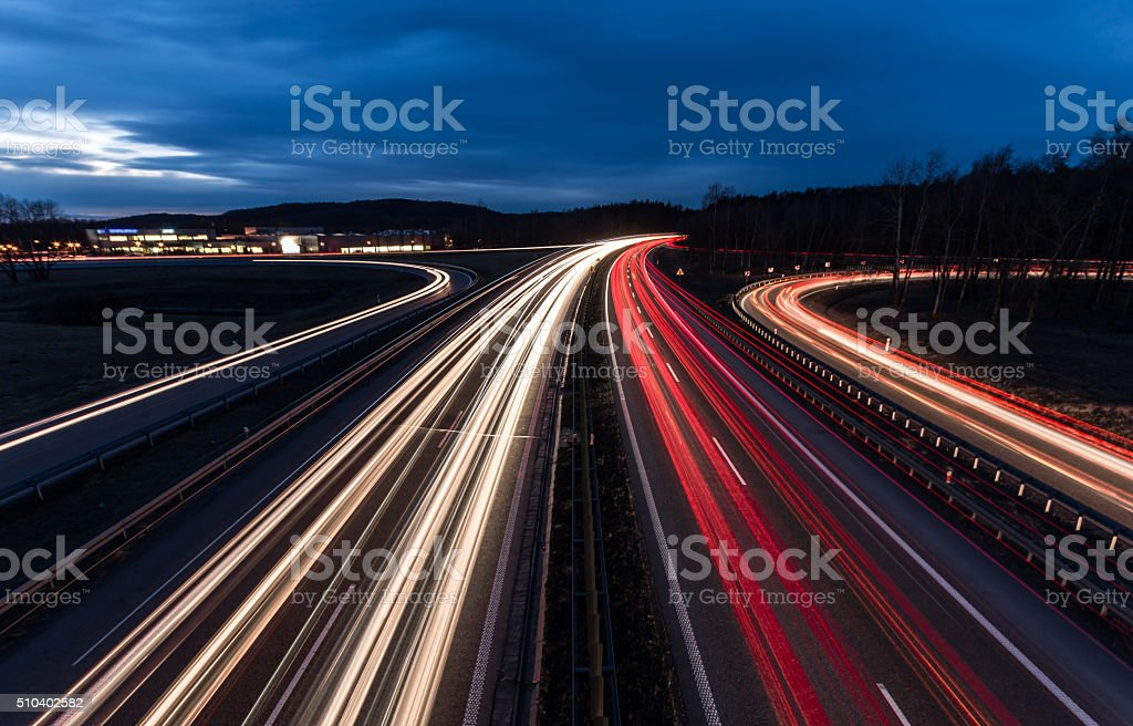white and red car light trails on motorway junction stock photo