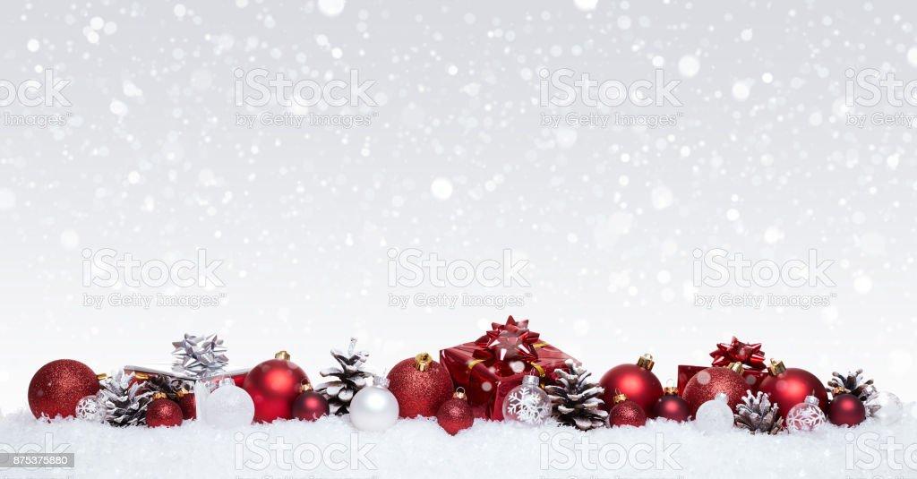 Weiße und rote Weihnachtskugeln mit Xmas Geschenke hintereinander isoliert auf Schnee – Foto