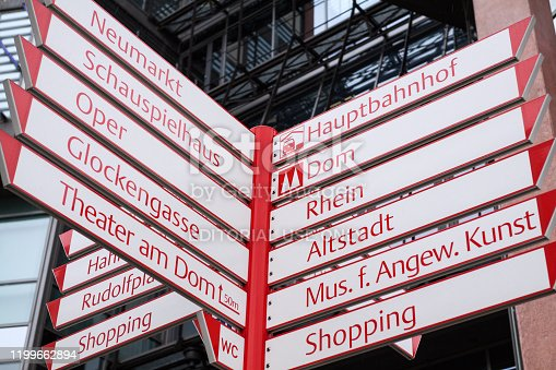 White and red colored arrows and fingerposts in Cologne near square Neumarkt with many directions and places named on arrows