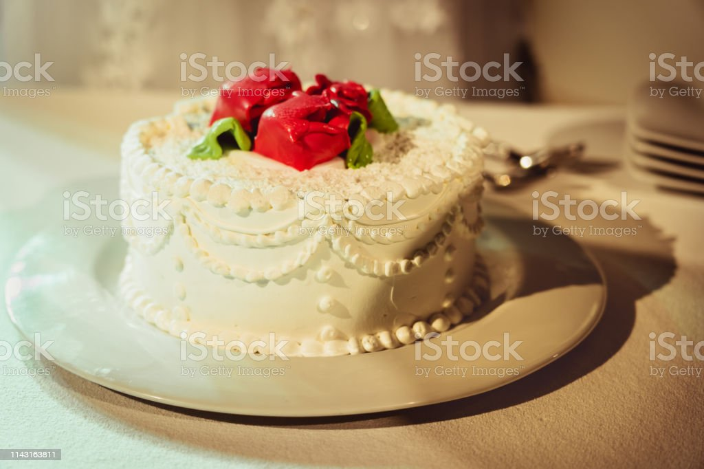 White, with icing and roses decorated wedding cake at wedding ceremony