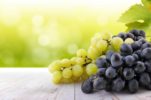 White and red grapes on table in vineyard