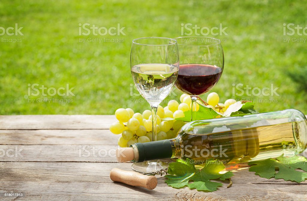 White and red wine glasses and bottle with bunch of grapes in sunny...