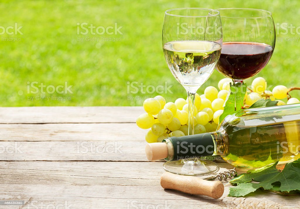 White and red wine glasses, wine bottle and white grape stock photo
