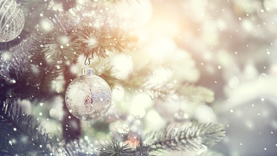 White and silver bauble hanging from a decorated Christmas tree with background.