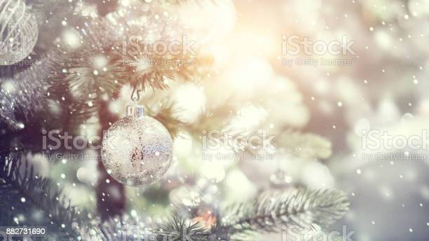 White and silver bauble hanging from a decorated christmas tree with picture id882731690?b=1&k=6&m=882731690&s=612x612&h=3diux73reybfwr2zgexsbbsldlejdgkzyjmpgfve810=