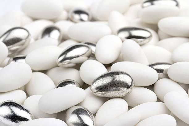white and silver sugared almonds stock photo