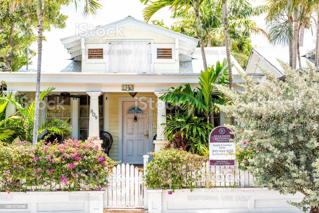 Branca e amarela arquitetura de casa na ilha de cidade Florida no curso, o dia ensolarado, o sinal para a venda de imóveis de propriedade de Berkshire Hathaway - foto de acervo