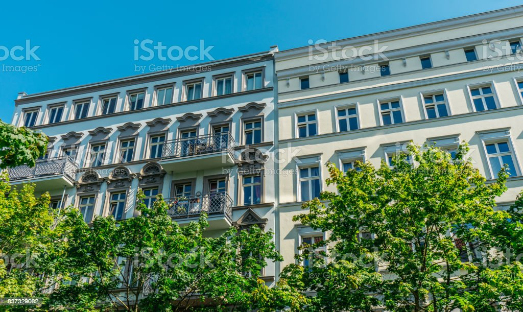 white and yellow buildings in a row with beautiful ornaments on their facades stock photo
