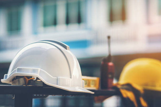 biały i żółty kask z wodą budowlaną, rękawice i radio, które są umieszczone na stalowym ogrodzeniu domu. - kask ochronny odzież ochronna zdjęcia i obrazy z banku zdjęć