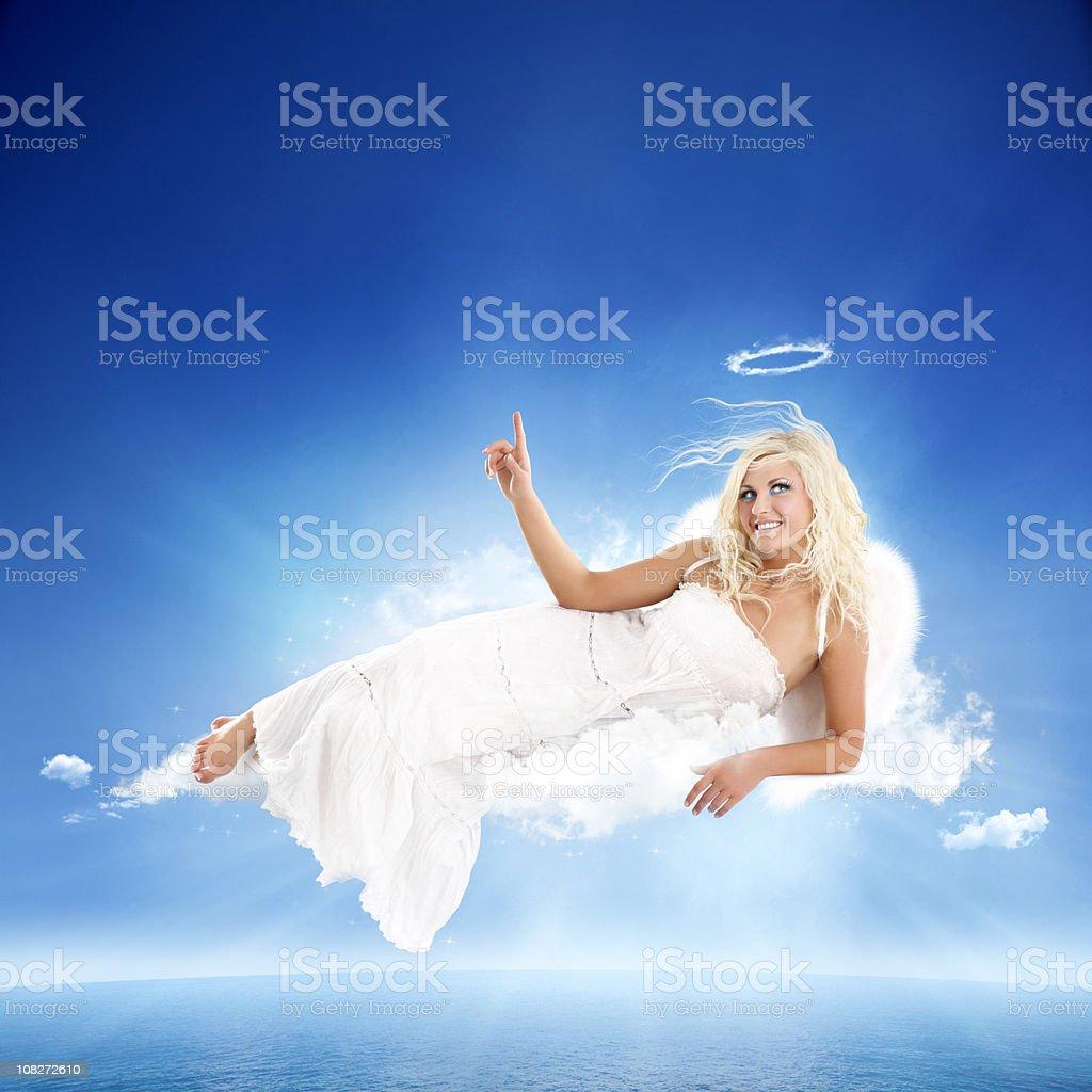 Weiße Engel auf dem Bauch liegen Wolke mit zeigt finger – Foto