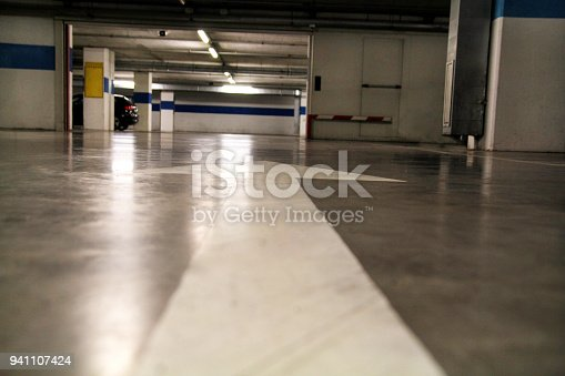 168589045 istock photo White arrow drawn on the ground in a parking / Old arrow street sign on road / Road traffic marking on street / Underground parking garage of a modern apartment house / Interior industrial building. 941107424