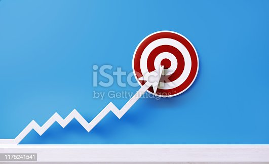 White arrow graph pointing a red bulls eye target on blue background. Horizontal composition with copy space.