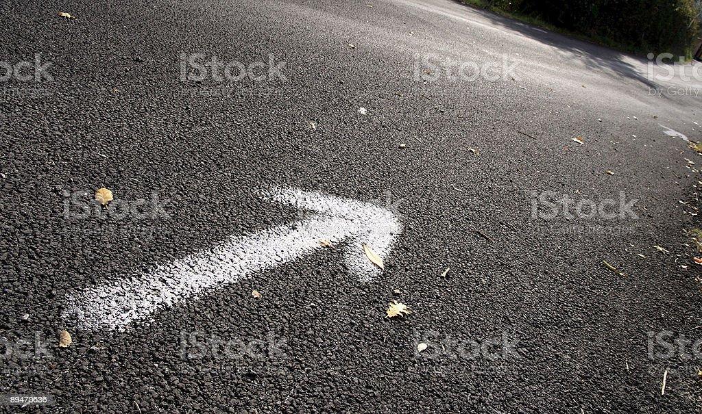 Weißen Pfeil auf dem Asphalt Straße Lizenzfreies stock-foto