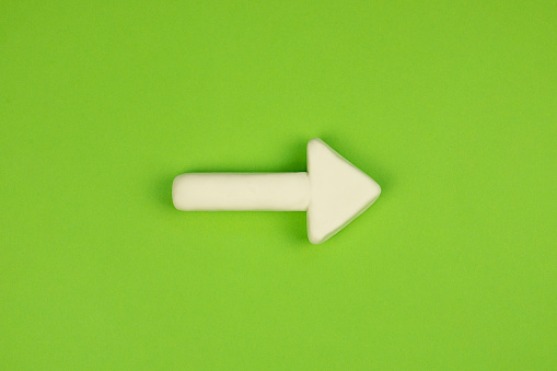 1023882582 istock photo White arrow on the green background. 3D mockup, pointing direction. Right way concept. 1226252823