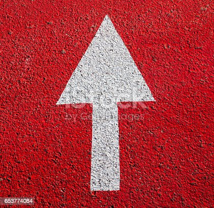 1023882582istockphoto White arrow on the red asphalt surface. 653774084