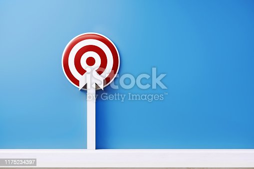 White arrow pointing a red bulls eye target on blue background. Horizontal composition with copy space.