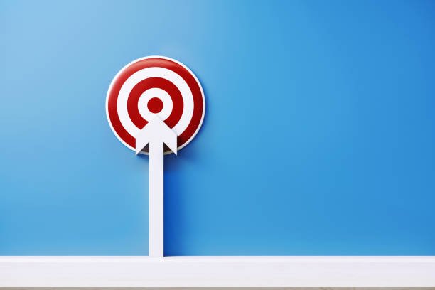 White Arrow Pointing  a Red Bulls Eye Target on Blue background stock photo