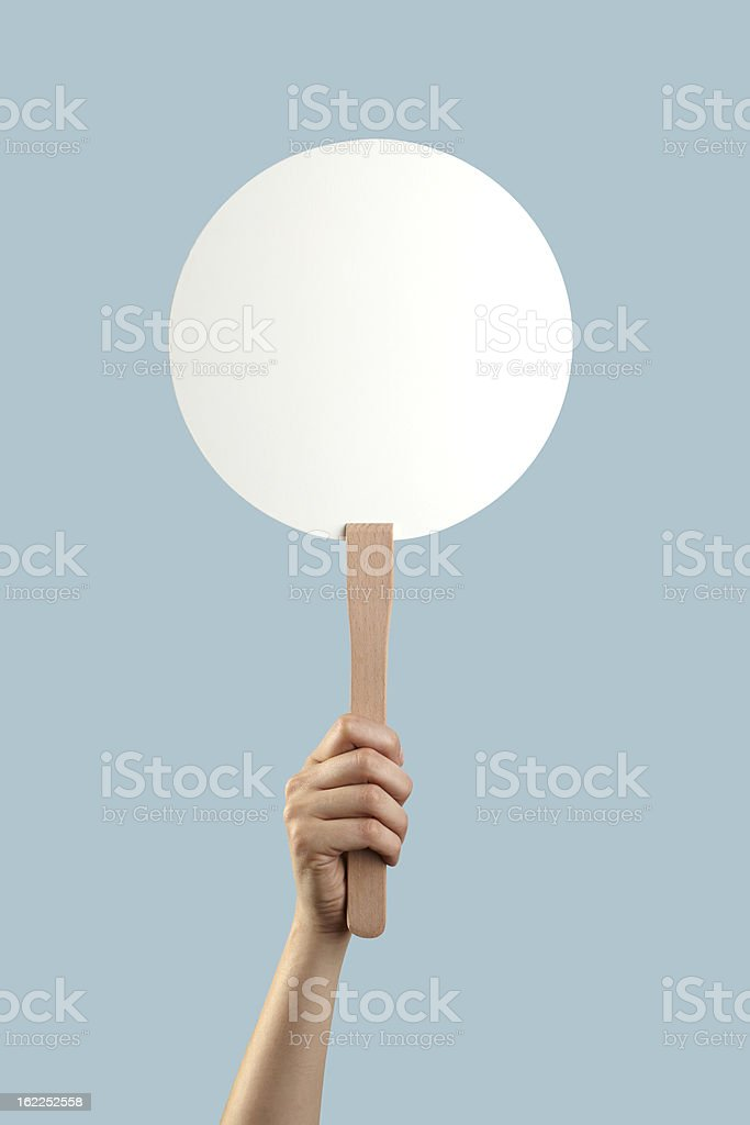 White auction placard with a hand holding it up stock photo