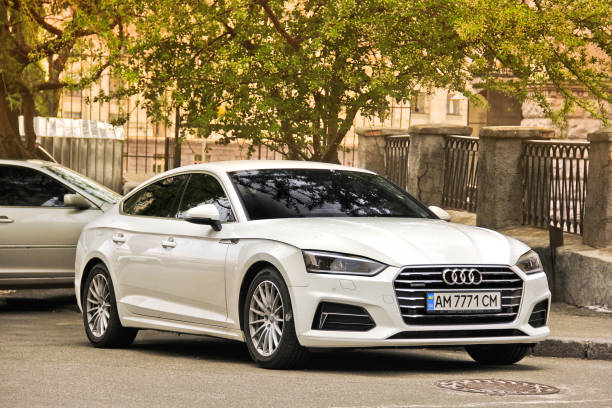 White Audi A5 parked in the city center against a tree stock photo