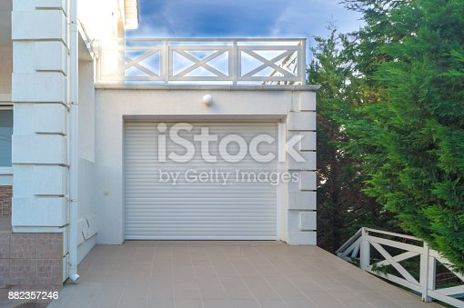 istock White automatic garage doors are closed on a sunny day 882357246