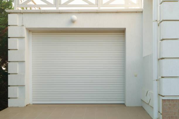 weiße automatische garagentore sind geschlossen - garagentor mit tür stock-fotos und bilder