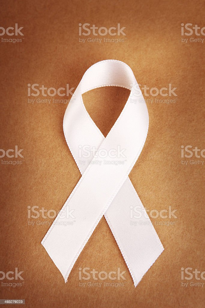 White Awareness Ribbon on Brown stock photo