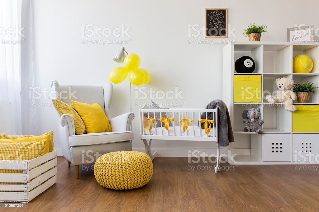 White furniture and yellow decorations in baby room interior