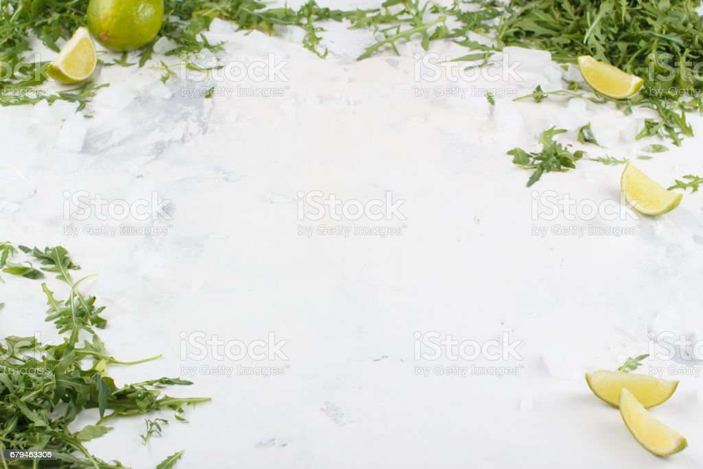 White background under your text. Limes and greenery of arugula on a white background. Frame for text. royalty-free stock photo