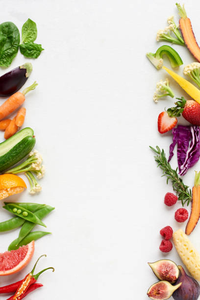 White background with colourful food border of raw fruit and vegetables stock photo