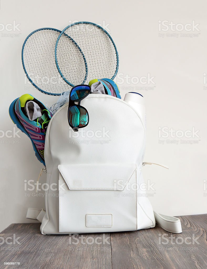 White bag with sport shoes, sunglasses and badminton battledore stock photo